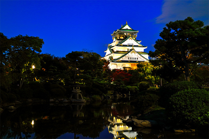 Osaka Castle is lit up at night